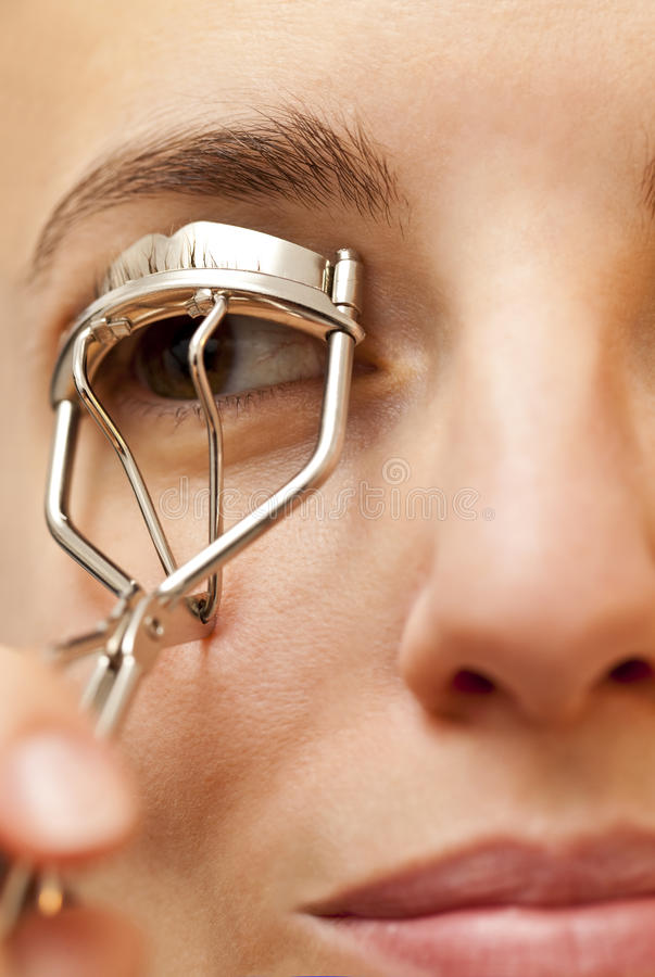 Portrait of young woman using an eyelash curler. Portrait of young and sensual woman using an eyelash curler royalty free stock image