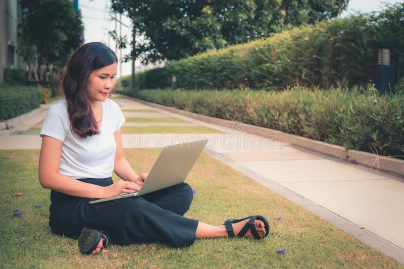 Portrait of young woman using laptop and sitting on garden grass stock image