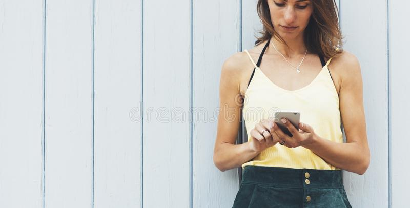 Portrait young women using smart phone isolated on background vintage wooden boards wall background mock up, pretty hipster female stock photo
