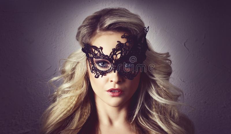 Portrait of young woman in vintage mask. Attractive blond girl with beautiful hairstyle. royalty free stock photo