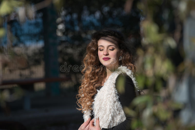 Portrait of a young woman wear sleeveless sheep coat. Enjoying the sunny day, closed eyes feeling the warm sun royalty free stock photography