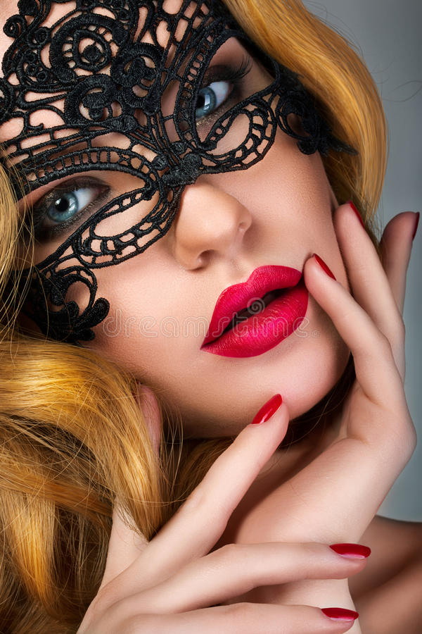 Portrait of young woman wearing black lace party mask stock photos