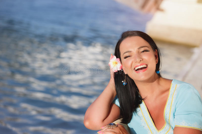 Portrait of young woman wearing flowers sitting on the beach royalty free stock photo