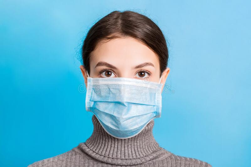 Portrait of young woman wearing medical mask at blue background. Protect your health. concept.  royalty free stock photography