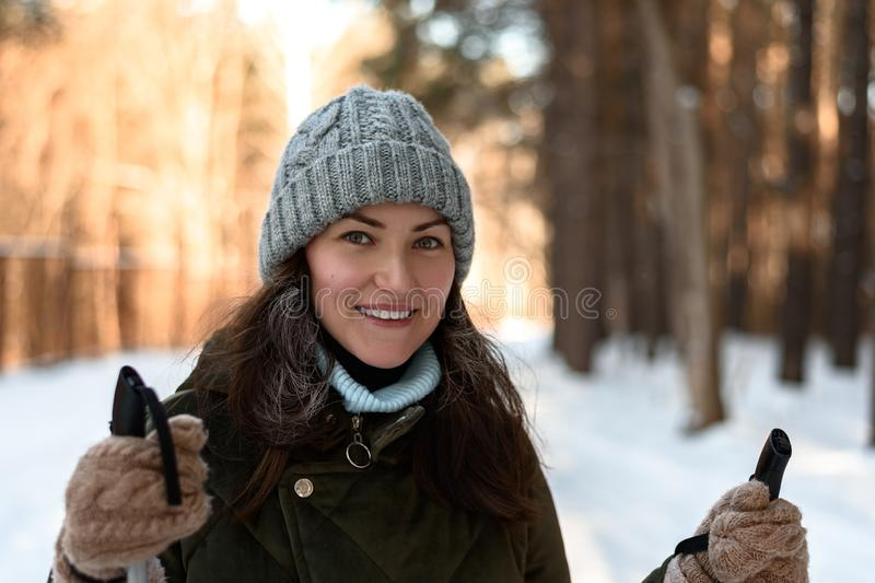 Portrait of a young woman in winter clothes in the winter forest. A woman is skiing in winter in the forest, love to the healthy w stock photography