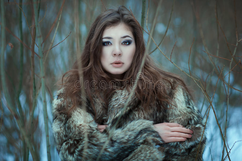 Portrait of a young woman in winter park. royalty free stock photography