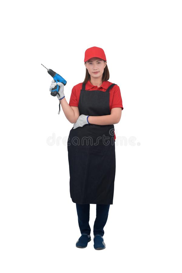 Portrait of young woman worker smiling in red uniform with apron, glove hand holding electric drill isolated on white backround royalty free stock images