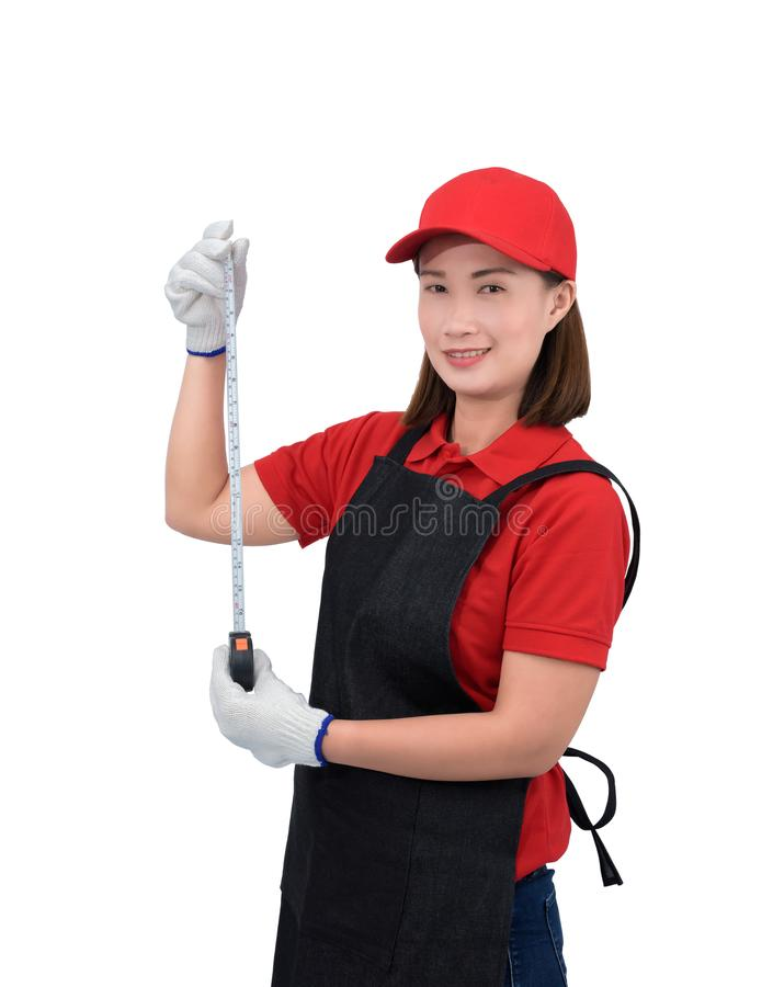 Portrait of young woman worker smiling in red uniform with apron, glove hand holding Measuring Tape isolated on white backround royalty free stock photos