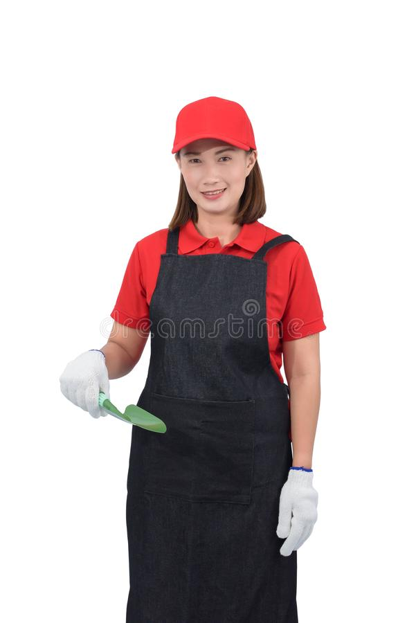 Portrait of young woman worker smiling in red uniform with apron, glove hand holding shovel isolated on white backround royalty free stock images