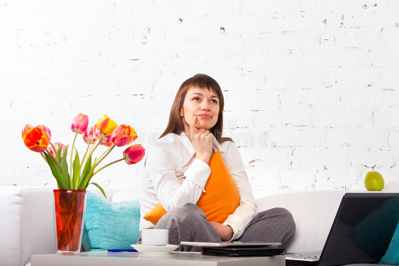 Portrait of a young woman working at home. Portrait of a young woman working on a laptop while sitting on the sofa stock image