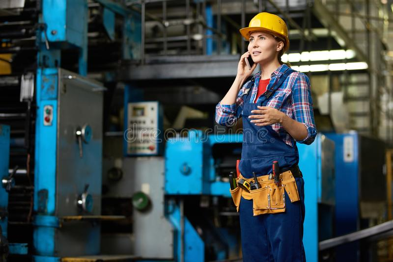 Female Worker Speaking by Phone in Factory Workshop. Portrait of young woman working in modern factory speaking by phone between rows of machines, copy space stock photo