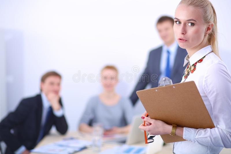 Portrait of a young woman working at office standing with folder . Portrait of a young woman. Business woman. Portrait of a young women working at office royalty free stock photos