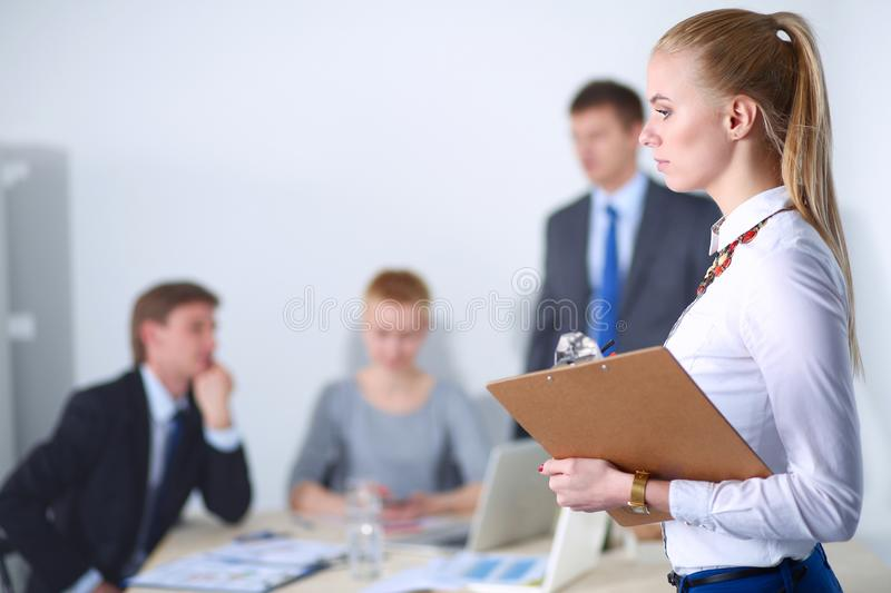 Portrait of a young woman working at office standing with folder . Portrait of a young woman. Business woman. Portrait of a young women working at office stock photos
