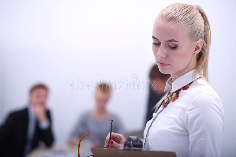 Portrait of a young woman working at office standing with folder . Portrait of a young woman. Business woman. Portrait of a young women working at office stock photo