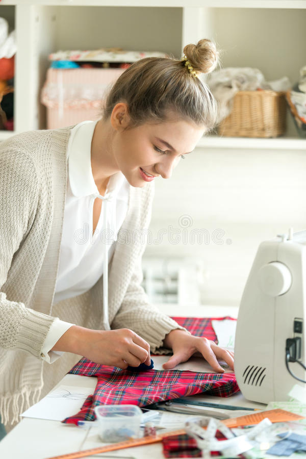 Portrait of a young woman working with a sewing pattern royalty free stock photography