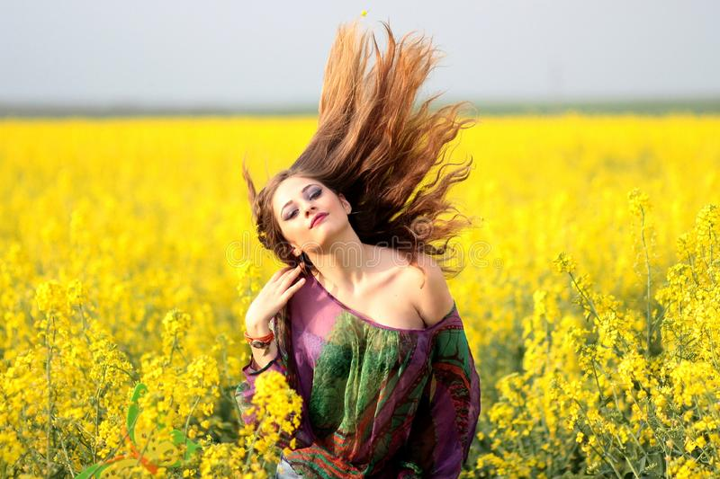 Portrait of Young Woman With Yellow Flowers in Field stock image