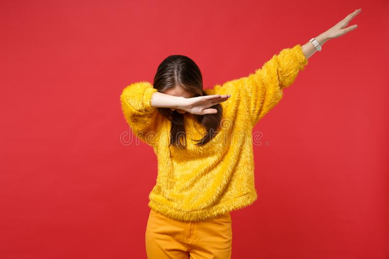 Portrait of young woman in yellow fur sweater with lowered head showing dab dance gesture isolated on bright red. Background in studio. People sincere emotions stock photos
