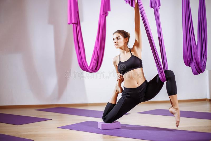 Portrait young women making antigravity yoga exercises. Aerial aero fly fitness trainer workout. Portrait young woman making antigravity yoga exercises. Aerial stock image
