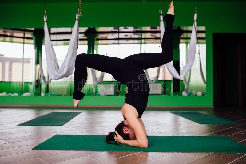 Portrait young women making antigravity yoga exercises. Aerial aero fly fitness trainer workout. white hammocks. royalty free stock image