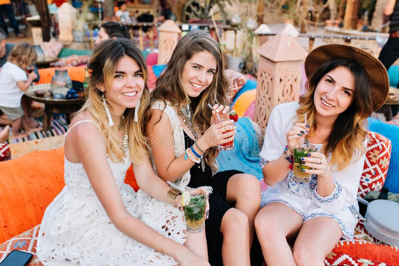 Portrait of young women spending time together after work and sitting in open-air restaurant with tasty cocktails. Three royalty free stock photo