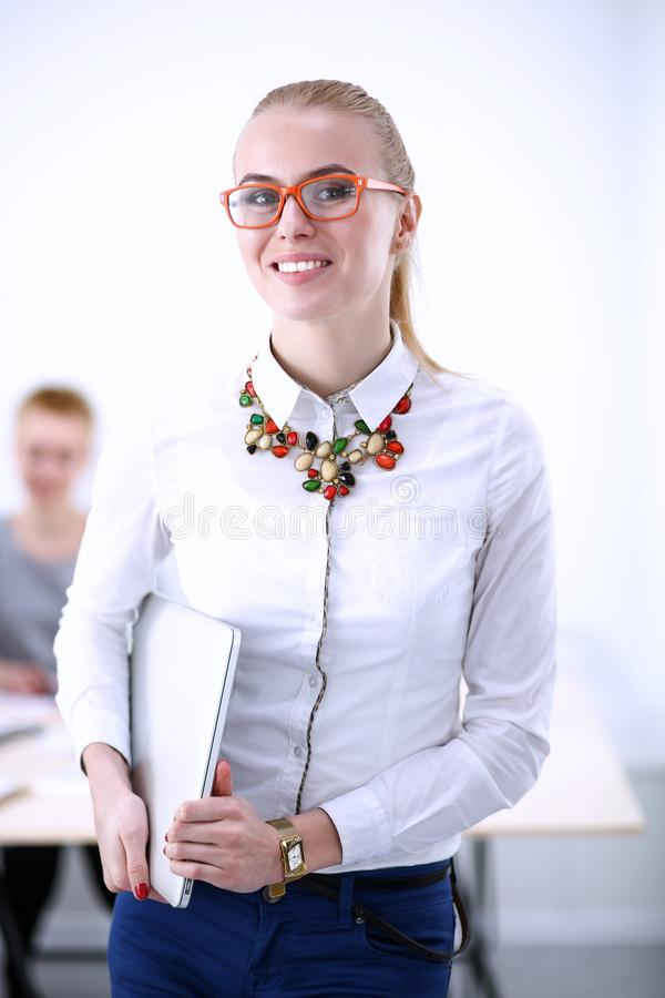 Portrait of a young woman working at office standing with folder . Portrait of a young woman. Business woman. Portrait of a young women working at office royalty free stock photo