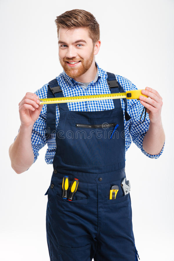 Portrait of young worker in uniform with yellow measuring tape royalty free stock photo