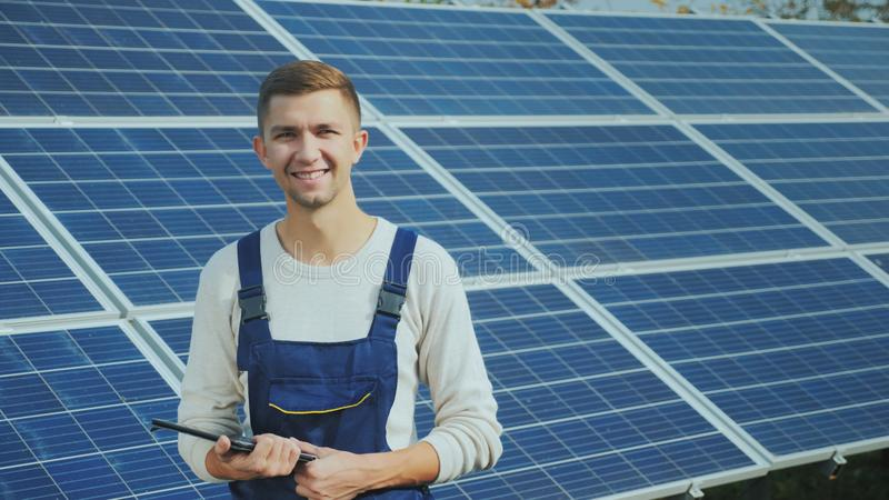 Portrait of a young worker in workwear, smiling and looking at the camera. Against the background of solar panels royalty free stock photos
