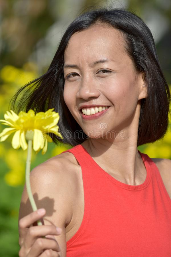 Portrait Of A Youthful Diverse Female With A Flower. An attractive and asian person stock photos