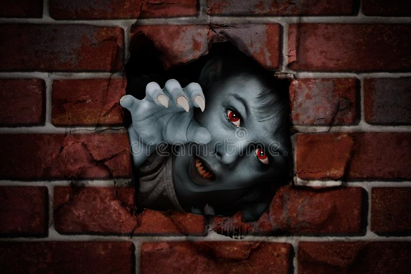 Portrait of a zombie boy. Peeking out of a hole in a brick wall royalty free stock image