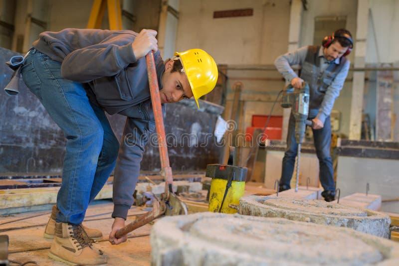 Portraitbauarbeiter, die Beton bohren lizenzfreies stockbild