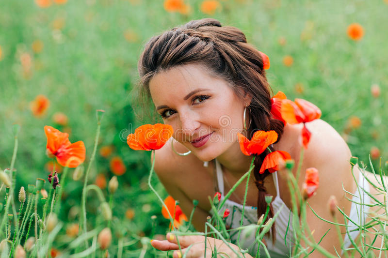 Portraite of beautiful girl in the poppy field stock image