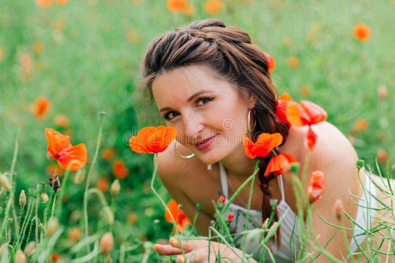 Portraite di bella ragazza nel campo del papavero immagine stock