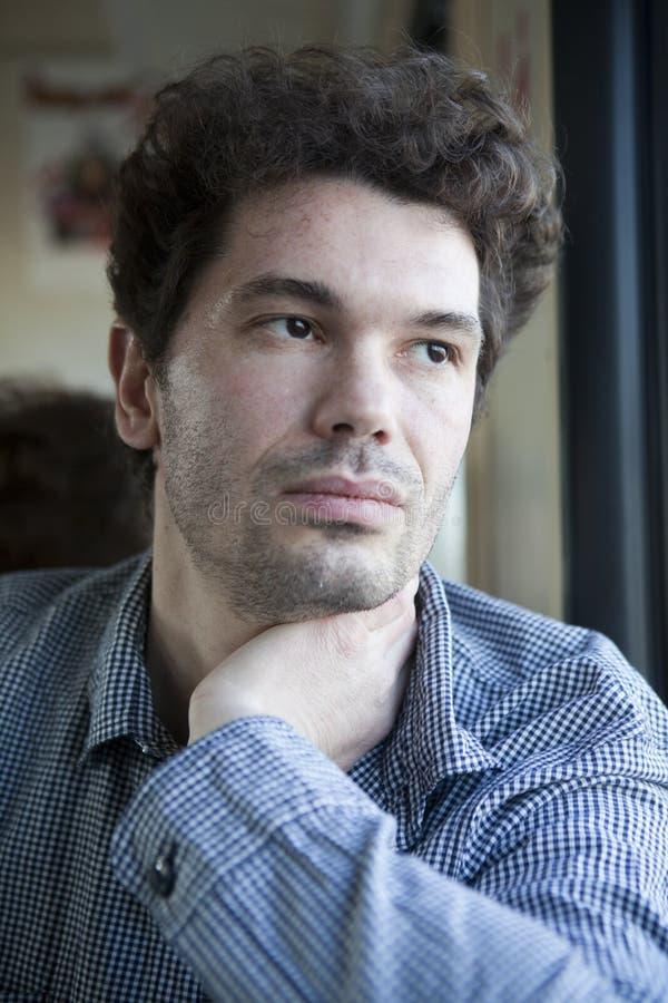 Portraitjunge-Rotationmann, der Fenster betrachtet stockfoto