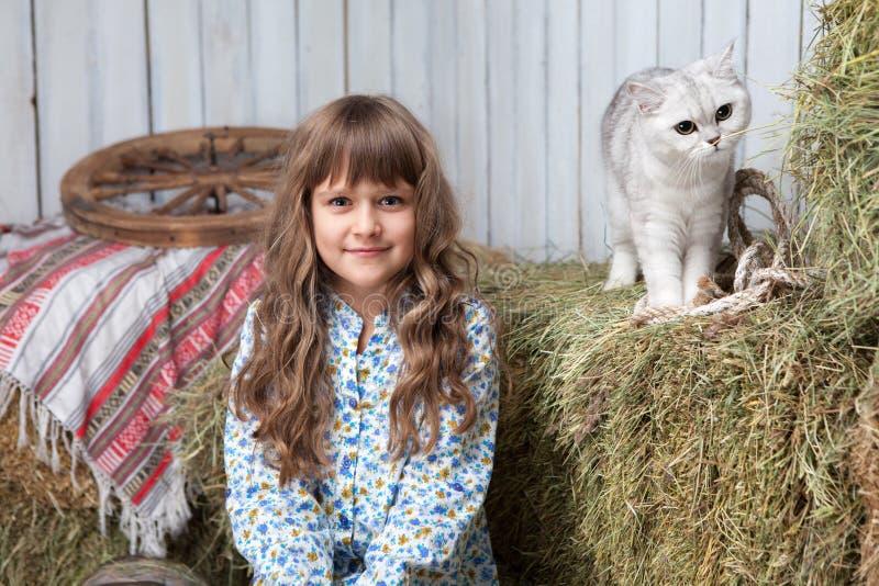 Portraitmädchendorfbewohner, Katze auf Heustapel im Stall lizenzfreies stockfoto