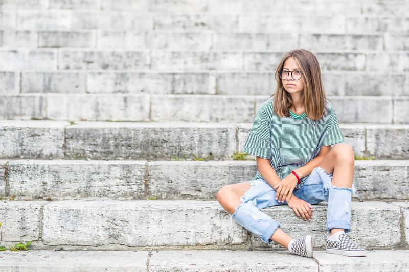 Portraito of young girl in a free modern outfit from jeans with holes stock photos