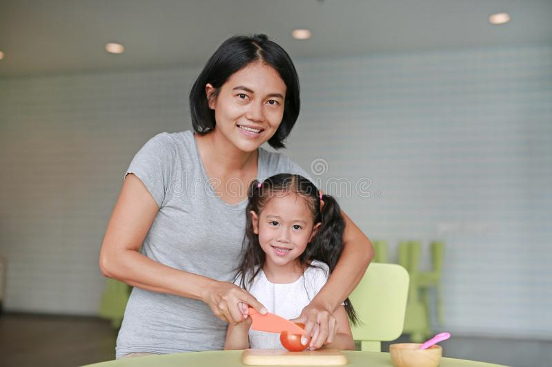 Portraits Asian mother and daughter slicing vegetable on chopping board at play room. Mother teaches her little child girl to royalty free stock photo