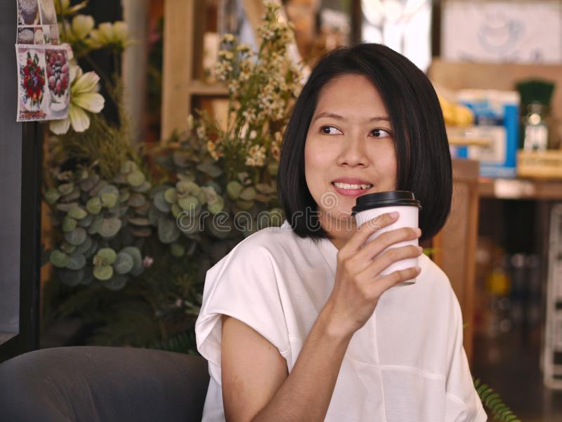 Portraits of Asian woman holding a cup of coffee looking to her right hand in cozy coffee shop. royalty free stock photography
