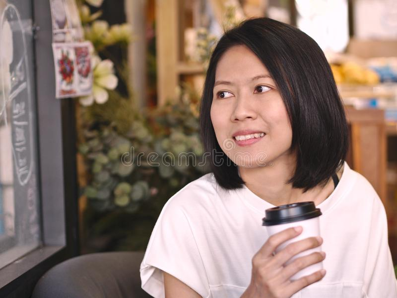 Portraits of Asian woman holding a cup of coffee looking to her right hand in cozy coffee shop. royalty free stock image