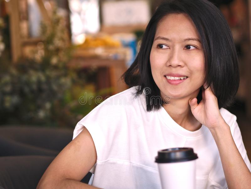 Portraits of Asian woman looking to her right hand with smile face in cozy coffee shop. stock image