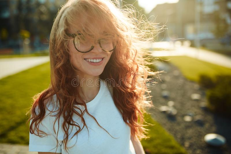 Portraits of a charming red-haired girl with a cute face. Girl posing for the camera in the city center. She has a wonderful mood stock photos
