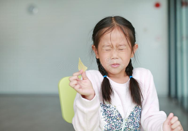 Portraits of cute Asian little girl eating crispy potato chips with face emotion feeling sour royalty free stock photo