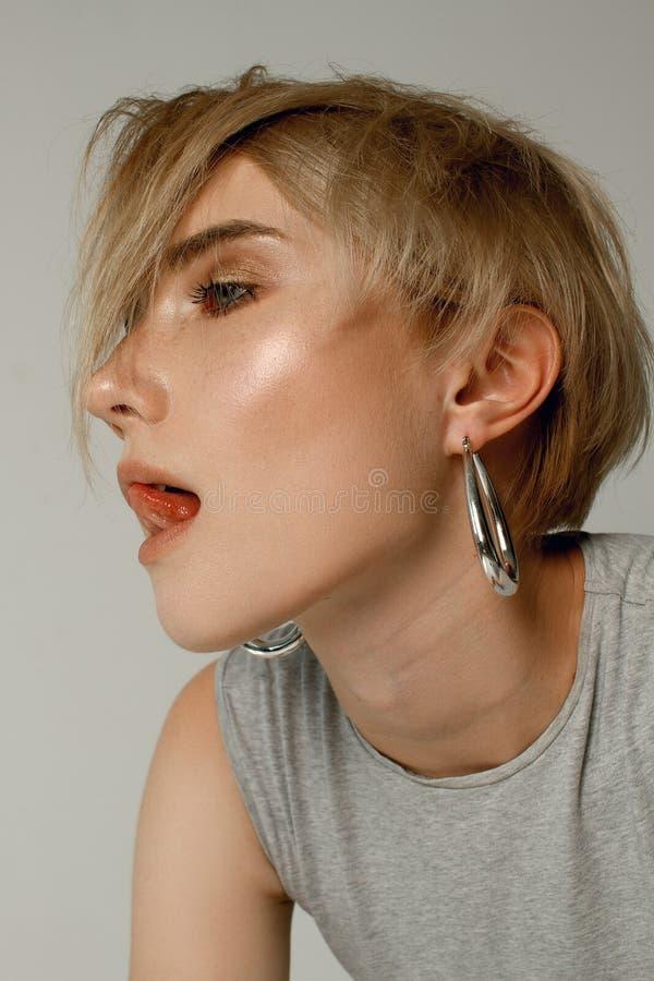 Portraits d'une belle fille avec une coiffure courte sur un fond blanc dans un T-shirt blanc images stock