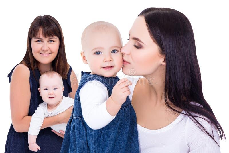 Portraits de deux jeunes m?res heureuses avec de petits enfants d'isolement sur le blanc photographie stock libre de droits