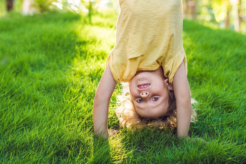 Portraits of happy kids playing upside down outdoors in summer park walking on hands stock image