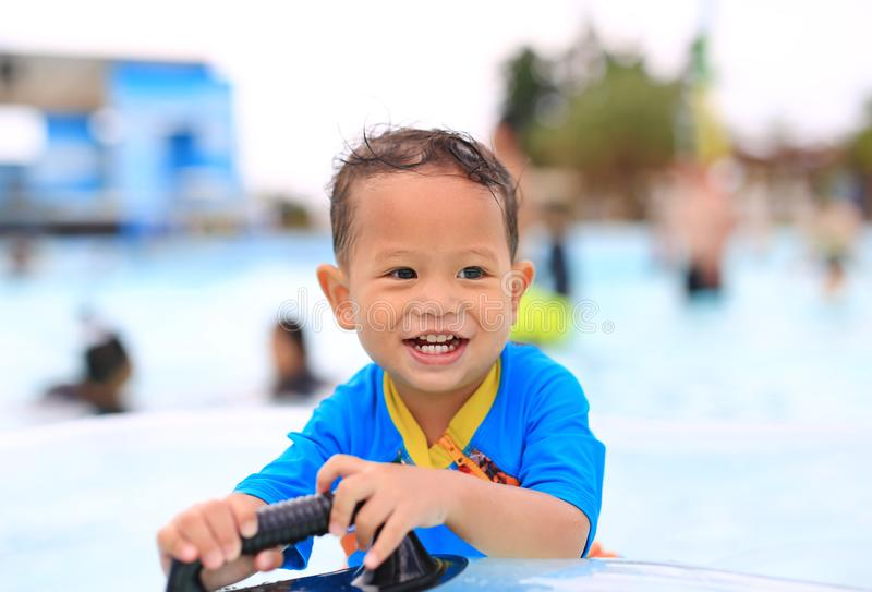 Portraits of happy little Asian baby boy smiling having fun at swimming pool outdoor royalty free stock images