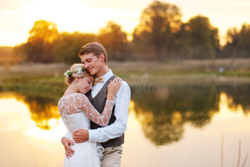Portraits of a newly married couple. The wedding couple is standing on the background of the order. Lovers are happy stock images