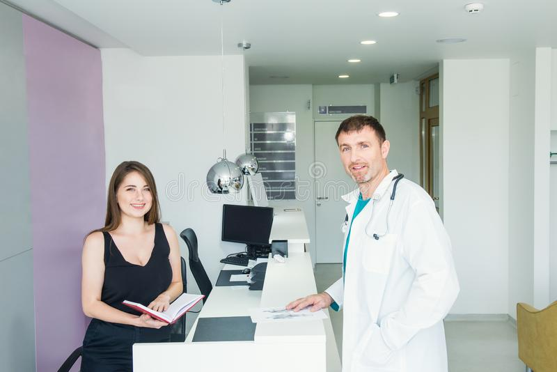 Portraits of smiling male doctor and young friendly female receptionist at hospital reception desk. Occupation, staff interaction royalty free stock image