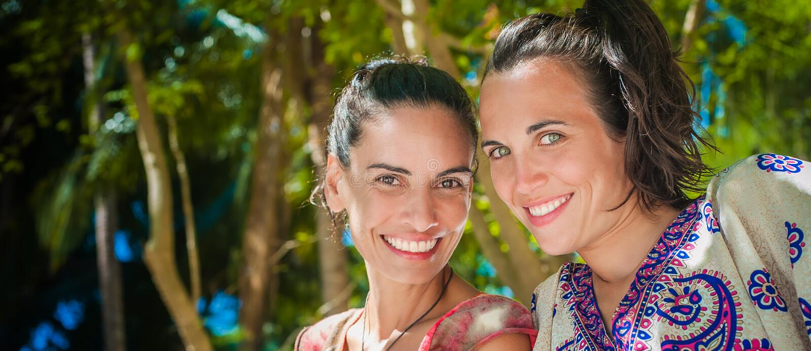 Two happy girlfriends smiling and enjoying on the beach royalty free stock photography