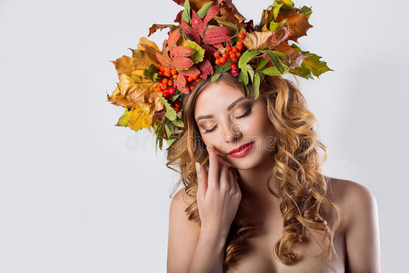 Portraiture style fashion beautiful girl with red hair fall with a wreath of colored leaves and mountain ash color bright tre. Ndy makeup in orange tones royalty free stock photos