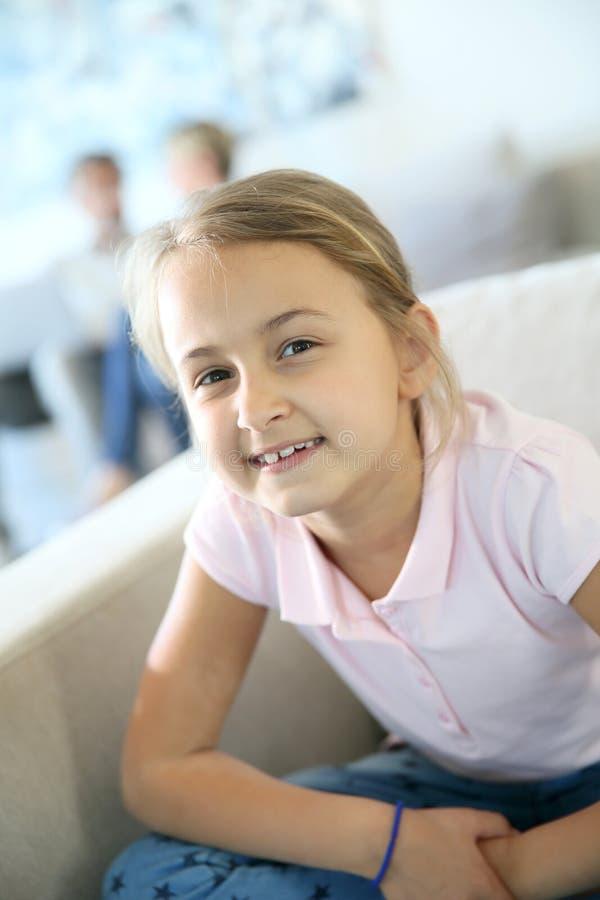 Portraot av att le liten flickasammanträde på soffan fotografering för bildbyråer